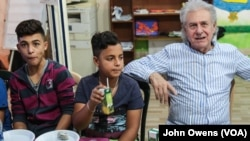 Jibril Latach, 16 and Lebanese, joins his best friend Raed Abdo, 14, a Syrian refugee from Homs, for post-rehearsal food and drinks with maestro Salim Sahab, Oct. 28, 2017, in Tripoli, Lebanon.