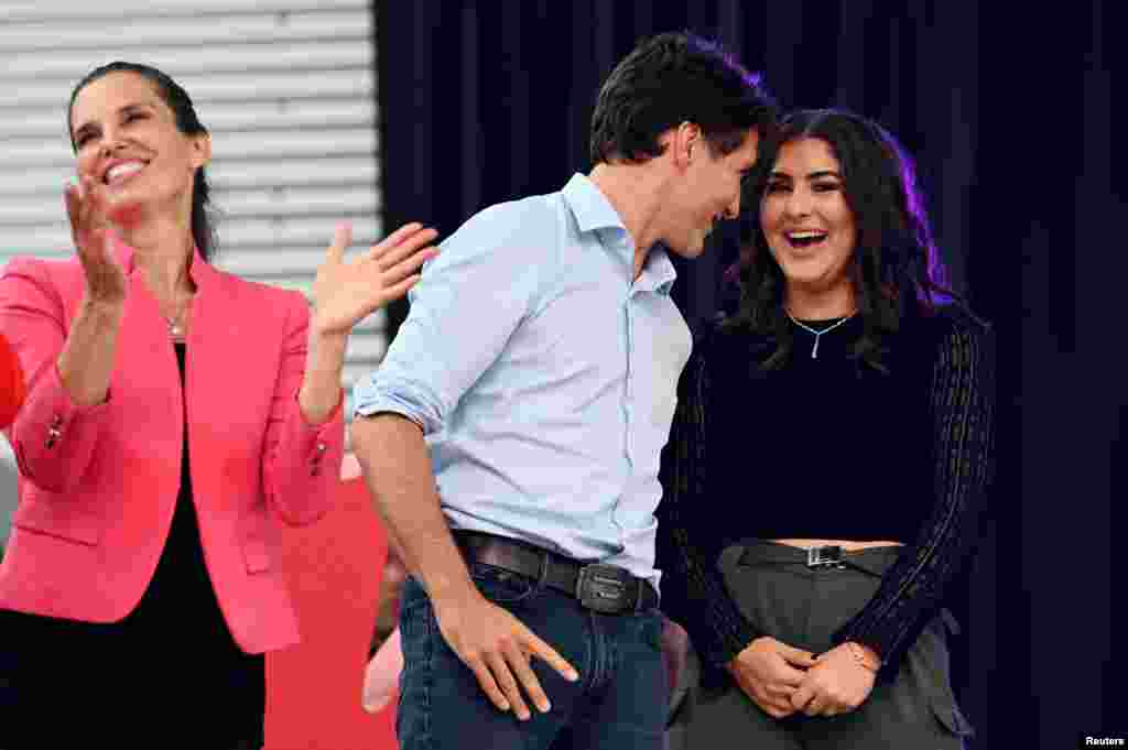 "Canada's Prime Minister Justin Trudeau speaks with U.S. Open tennis champion Bianca Andreescu as Canada's Minister of Science and Sport Kirsty Duncan (left) looks on at the ""She The North"" celebration rally for Andreescu in Mississauga, Ontario, Sept. 15, 2019."