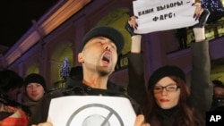 """Opposition activists, one of them holding a poster depicting Russian Prime Minister Vladimir and another a poster reading, """"Your election is a farce"""", shout slogans during a protest against vote rigging in St. Petersburg, Russia, December 4, 2011."""