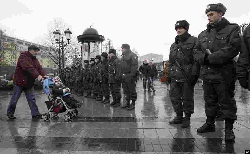 2011年12月4号,俄罗斯警察守卫在一个广场入口处,防止民众抗议者进入。背景是莫斯科大剧院。 (AP)