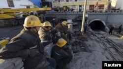 Regu penyelamat tengah beristirahat dekat pintu masuk pertambangan batu bara di Datong, provinsi Shanxi, China, yang dilanda banjir, 20 April 2015. (Foto: REUTERS/Stringer)
