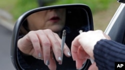 A woman smokes a cigarette while sitting in her truck in Hayneville, Alabama. March 2, 2013. (AP Photo/Dave Martin)