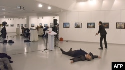 Andrei Karlov (2ndR), the Russian ambassador to Ankara, lies on the floor after being shot by a gunman (R) during an attack at a public event in Ankara, Turkey, Dec. 19, 2016.