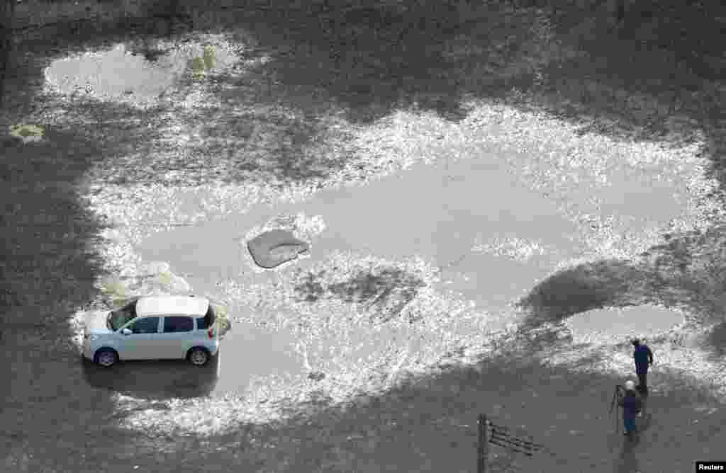 A car is seen trapped at the soil liquefaction caused by an earthquake near Tsuruoka station in Tsuruoka, Yamagata prefecture, Japan, in this photo taken by Kyodo.