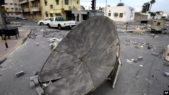 Cars drive past barricades set up by Bahraini demonstrators at a Shiite neighborhood in Manama on March 17, 2011