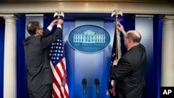 Dos empleados de la Casa Blanca preparan las banderas antes de la llegada del presidente Barack Obama a la sala de crisis sobre Ucrania.