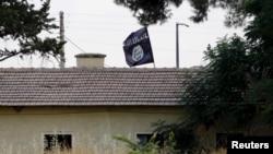 Bendera ISIS terlihat di atas kantor bea cukai di perbatasan di Jarablus, Suriah, terlihat dari Karkamis, di provinsi Gaziantep, Turki (1/8).
