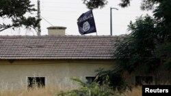 Hình tư liệu - Một lá cờ Nhà nước Hồi giáo treo tại cơ quan hải quan cửa khẩu Jarablus, Syria.