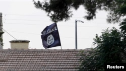 FILE - An Islamic State flag flies over the customs office of Syria's Jarablus border gate, Aug. 1, 2015. A Maryland man has been detained on federal charges in connection with the IS group.