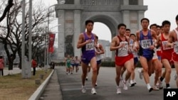 FILE - A crowd of runners passes by the Arch of Triumph in Pyongyang, North Korea during the IAAF-25th Mangyongdae Prize Marathon, April 2012.