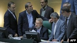 FILE - Iranian Parliament Speaker Ali Larijani (C), surrounded by lawmakers, speaks during a session in the capital Tehran, Aug. 28, 2018.