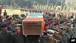 Indian Border Security Force officers carry the coffin of a colleague killed Wednesday in an India-Pakistan cross-border firing in the disputed Kashmir region, in Jammu, India, Jan. 1, 2015.