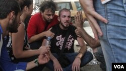 A man is consoled after seeing the tents of hunger protestors destroyed by a self-identified group supporting Lebanese government Speaker and Amal party leader Nabih Berri, Sept. 16, 2015. (J. Owens/VOA)