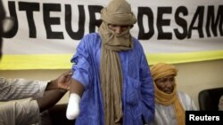 A victim of forced hand amputation by al-Qaida-linked Islamist group Movement for Unity and Jihad under Sharia law as punishment for stealing livestock, Alhader Ag Mahamoud, 30, attends a news conference organized by Amnesty International in Bamako, Mali,