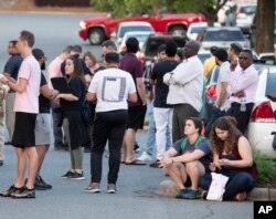 People gather across from the campus of UNC Charlotte after a shooting incident at the school, April 30, 2019, in Charlotte, N.C.