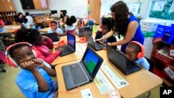 Second grade student Khalil Morgan, left, reacts after completing an interactive math problem on his computer, with teacher Jillian Martin, standing to the right, at Turner Elementary School in southeast Washington, Tuesday, Aug. 29, 2017. (AP Photo/Manuel Balce Ceneta)