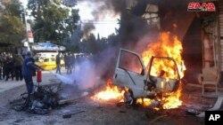 22일 시리아 해안도시 라타키아 알함맘 광장에서 차량 폭발 사고가 발생한 후 남성이 소화기로 화재를 진압하고 있다.