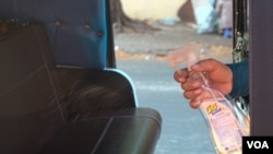 A tuk tuk driver sanitizes the seats after a ride to prevent the spread of COVID-19 in Phnom Penh, Cambodia, on March 28, 2020. (Khan Sokummono/VOA Khmer)