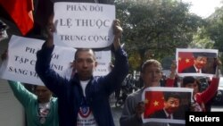 FILE - Protesters hold marked images of Chinese President Xi Jinping and anti-China signs during a protest ahead of his visit to Vietnam, on the street in Hanoi, Nov. 3, 2015.