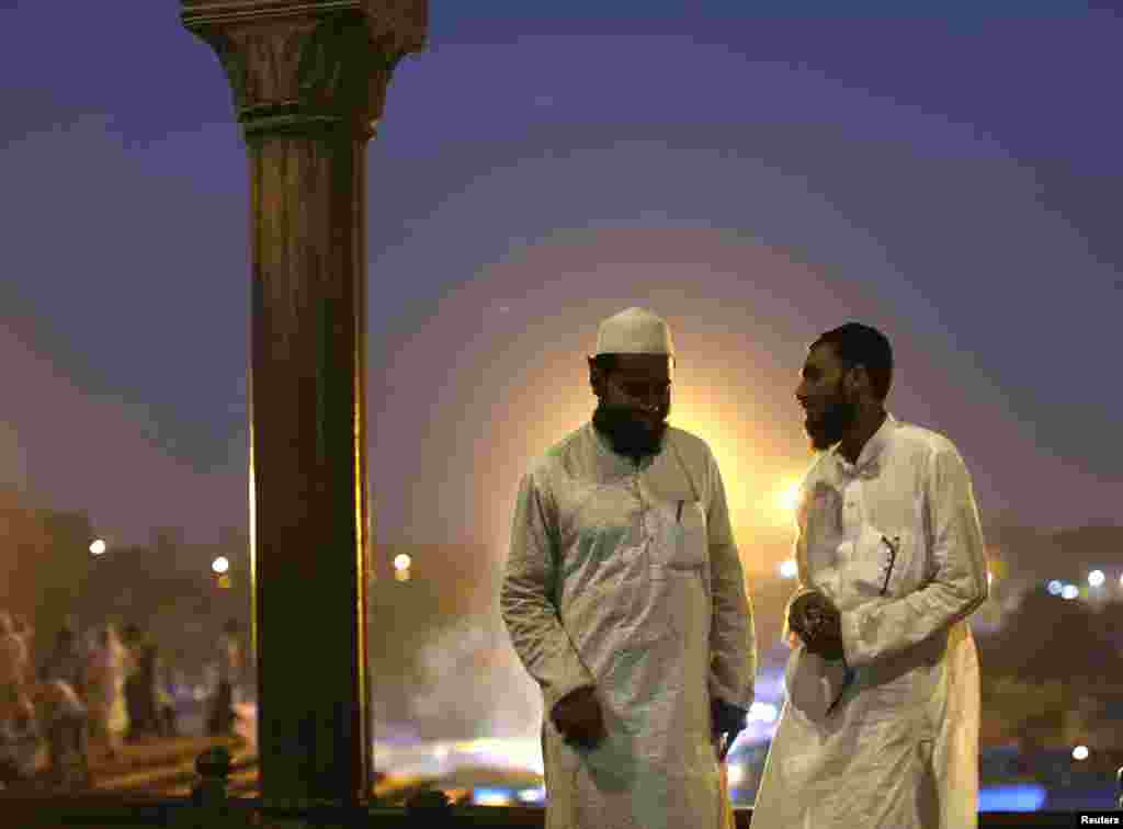 Muslims relax outdoors after having their Iftar, or breaking of the fast meal, on the first day of the holy month of Ramadan in India, at the Grand Mosque, in the old quarters of Delhi, India, June 30, 2014.