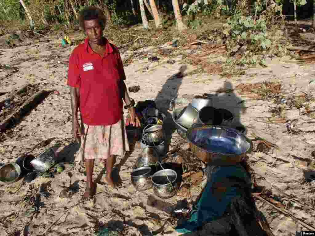 A villager collects belongings after a tsunami hit Venga village on Solomon Islands, Feb. 7, 2013. (World Vision)