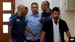 Former Israeli cabinet minister indicted on suspicion of spying for Iran, Gonen Segev, center, is escorted by prison guards as he arrives at court in Jerusalem, Israel, July 5, 2018.