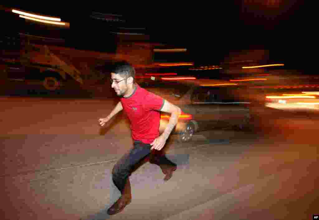 A protester runs for shelter after Bahraini security forces opened fire at protesters marching towards the Pearl Square in capital Manama. (Reuters/Hamad I Mohammed)