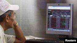Nhà đầu tư nhìn vào màn hình thông tin chứng khoán tại trung tâm chứng khoán ở Hà Nội.