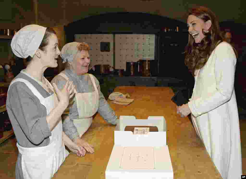 Britain's Duchess of Cambridge, Kate Middleton, chats to cast members Sopie McShera, left, and Lesley Nicol during an official visit to the set of the TV series Downton Abbey at Ealing Studios in London.