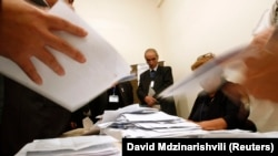 FILE - Election officials count ballots at the polling station during the presidential elections in Baku, Oct. 9, 2013.