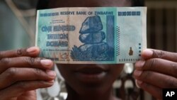 FILE - A woman holds a 100 trillion-dollar note in Harare, the highest denomination printed by the Reserve Bank of Zimbabwe.