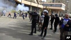 Một sĩ quan cảnh sát chống bạo động Ai Cập bắn hơi cay vào người biểu tình trong cuộc đụng độ gần Quảng trường Tahrir, Cairo, ngày 27/1/2013.