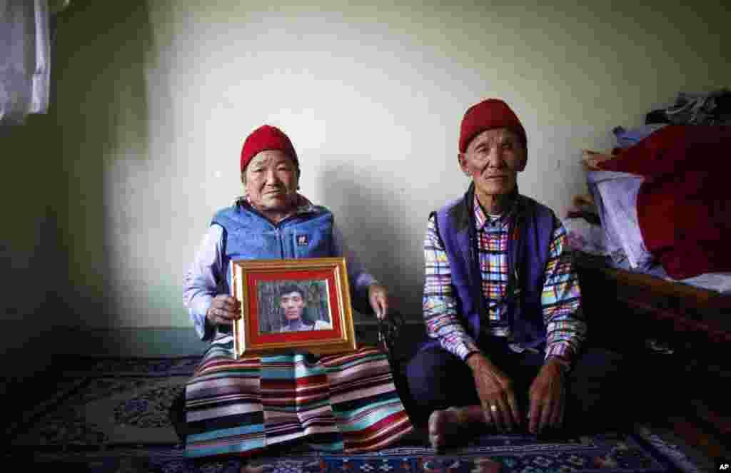 Nimdige Sherpa memegang foto putranya Ang Kaji Sherpa yang tewas dalam salju longsor di Gunung Everest, bersama suaminya Ankchu Sherpa di dalam apartemen mereka di Katmandu, Nepal (23/4). (AP/Niranjan Shrestha)