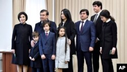 FILE - President Shavkat Mirziyoyev poses with his family after voting during the presidential election, Tashkent, Uzbekistan, Dec. 4, 2016.