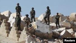 Tentara Suriah berdiri di atas puing-puing Kuil Bel di kota kuno bersejarah Palmyra di provinsi Homs, Suriah. (Foto: Dok)