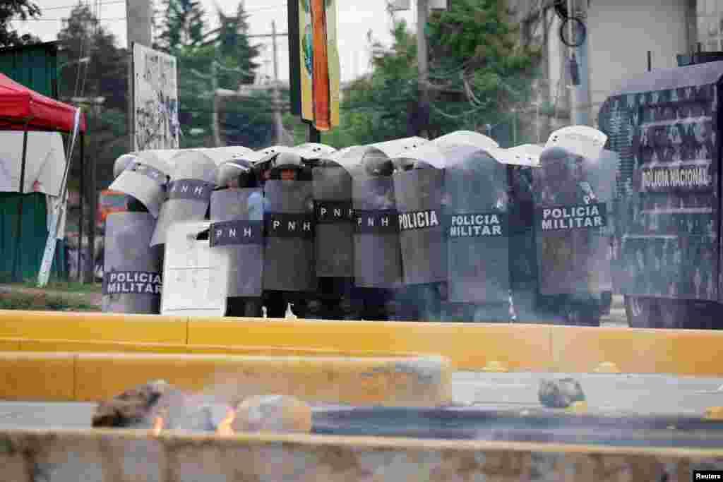 ប៉ូលិសកុបកម្មការពារខ្លួនជាមួយនឹងខែលរបស់ពួកគេនៅក្នុងបាតុកម្មមួយប្រឆាំងនឹងការឡើងថ្លៃប្រេង និងថាមពេល នៅក្នុងក្រុង Tegucigalpa ប្រទេសហុងឌូរ៉ាស កាលពីថ្ងៃទី២ ខែមិថុនា ឆ្នាំ២០១៨។
