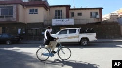 FILE - An Afghan man rides his bicycle in front of the office of the Agency Coordinating Body for Afghan Relief (ACBAR) in Kabul, Afghanistan, Nov. 6, 2016. Criminal gangs in Afghanistan often kidnap foreign aid workers, sometimes selling them to insurgents.