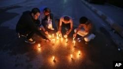 Những nhà báo Iraq thắp nến tại nơi văn phòng trưởng của đài Iraq Tự do bị bắn chết, ngày 22 tháng 3, 2014.