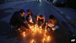 خبرنگاران عراقی در محلی که نگهبان کاخ ریاست جمهوری همکارشان را از پا درآورد، شمع روشن کرده اند - بغداد، ۲۳ مارس ۲۰۱۴