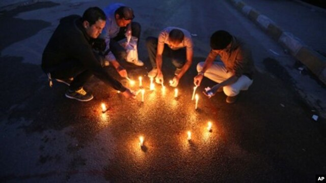 Iraqi journalists light candles where, according to police, a Kurdish officer of the Iraqi president's guard shot dead the bureau chief of a local radio station in Baghdad, March 22, 2014.