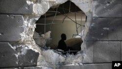 غزی کی پٹی میں ایک رہائشی عمارت پر ہونے والے فضائی حملے کے بعد دیوار میں پڑنے والے شگاف سے اندر کا منظر دیکھا جا سکتا ہے ۔ چودہ مئی دو ہزار اکیس