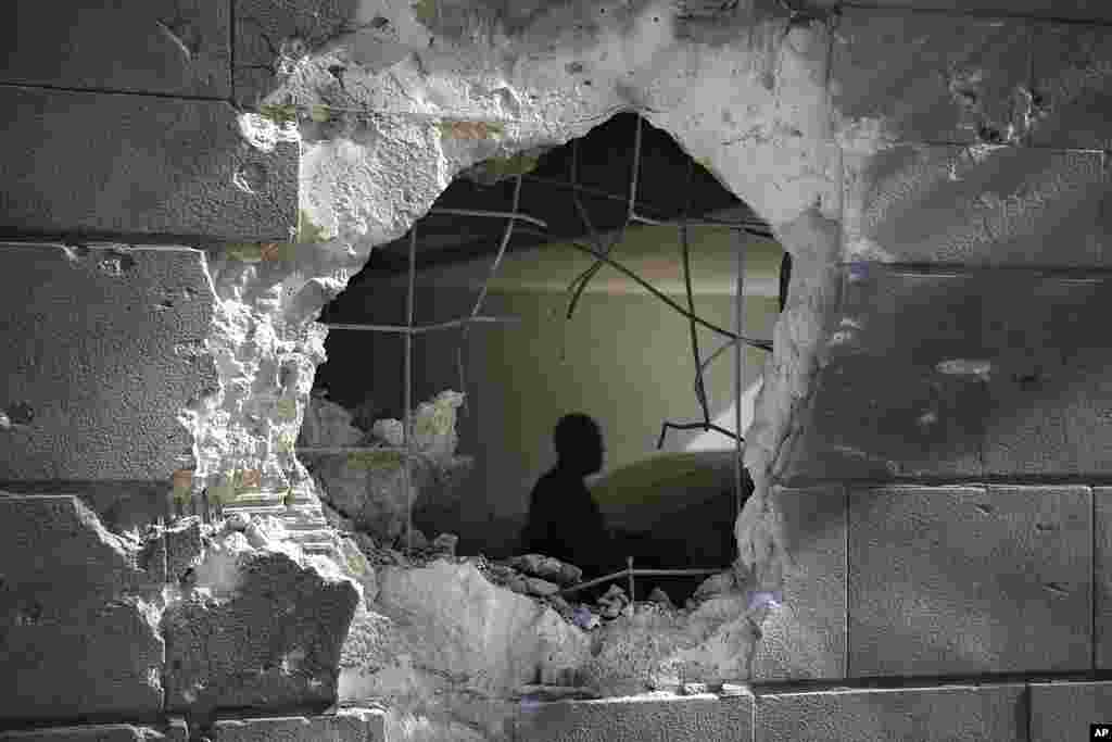 A man is seen trough a hole in a wall of a residential building after it was struck by a rocket fired from the Gaza Strip in Ashkelon, Israel.