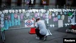 Seorang perempuan berdoa mengenang korban pemboman marathon di sebuah tempat peringatan bagi para korban di kota Boston (18/4).