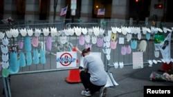 一名婦人在掛滿波士頓馬拉松賽爆炸案受害者名字的欄杆前曲膝哭泣悼念。