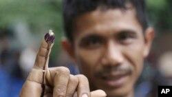 Seorang pria menunjukkan jarinya usai memberikan suara di salah satu TPS di Jakarta, Rabu (15/2).