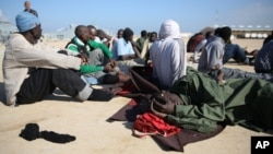 African migrants rest after their rescue by the Libyan Coast Guard west of Tripoli, Dec. 21, 2015.