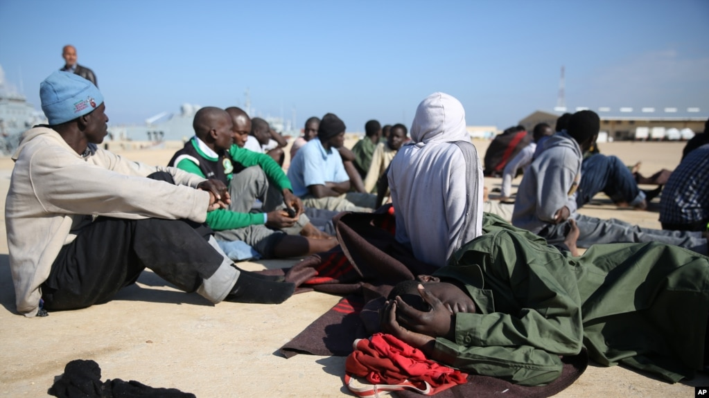 FILE - African migrants rest after their rescue by the Libyan Coast Guard west of Tripoli, Dec. 21, 2015.