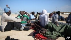 FILE - African migrants rest after their rescue by the Libyan Coast Guard west of Tripoli, Dec. 21, 2015. The International Organization for Migration says it is scaling up the repatriation of African migrants suffering abuse and exploitation in Libya, mainly at the hands of the police and the militias.