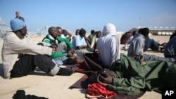 Wahamiaji wa Kiafrika wakipumzika baada ya kuokolewa nje ya mwambao wa Libya.