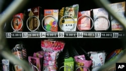 FILE - Condoms are seen above chewing gum and food snacks in a vending machine in China, Sept. 23, 2007.